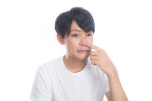 鼻を指さして困った顔をしている男性の写真