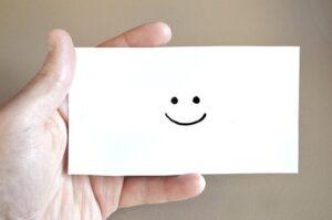 ニコニコの顔が描かれた名刺サイズの紙を持っている写真