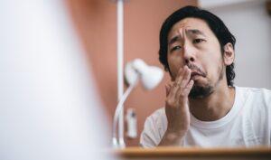 鏡の前で鼻を気にする男性
