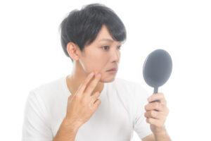 鏡をみて頬を気にする男性の写真