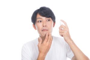 顔にスプレーを吹きかける男性の写真
